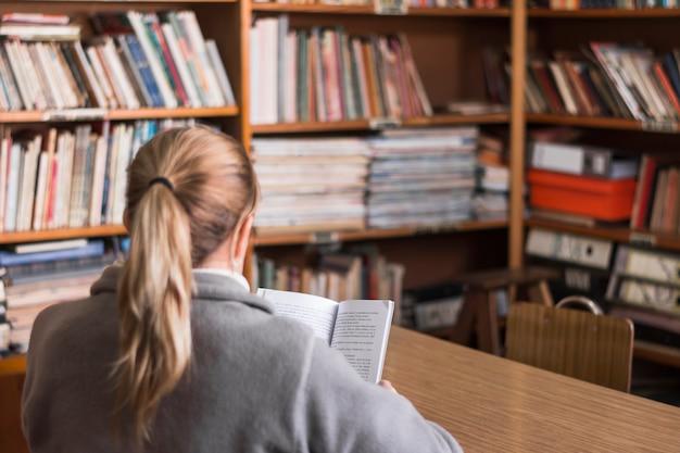 Femme anonyme lisant dans la bibliothèque