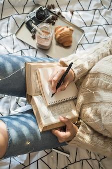 Femme anonyme prenant des notes pendant le petit déjeuner