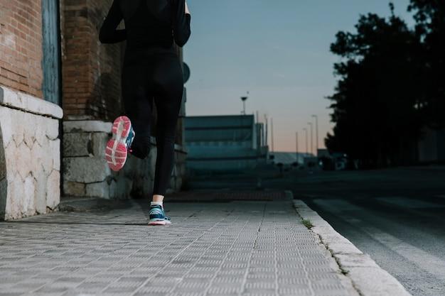 Femme anonyme qui court dans la rue au crépuscule
