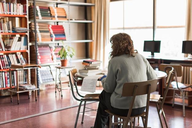 Femme anonyme travaillant dans la bibliothèque
