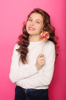 Femme avec un appareil dentaire tenant une sucette