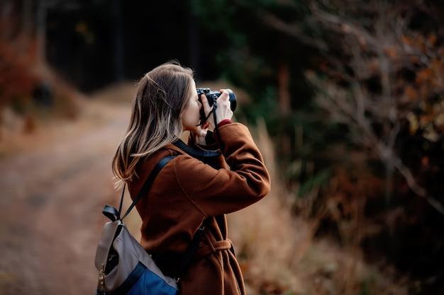 Femme avec appareil photo fait une photo dans la forêt de montagne