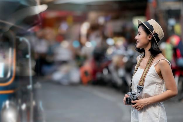 Femme avec appareil photo vintage debout dans la ville en vacances.