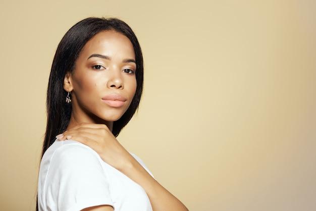 Femme d'apparence africaine cheveux longs foncés maquillage mode fond beige