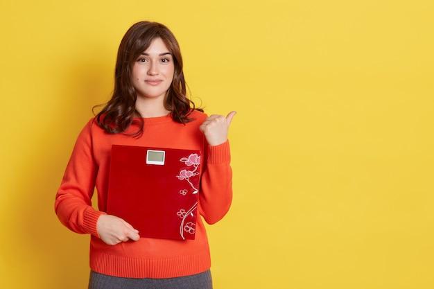 Femme avec une apparence agréable et des cheveux foncés tenant une balance au sol dans les mains, a une expression calme, pointant du doigt, copie espace, isolée sur un mur jaune.
