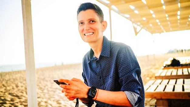 Une femme d'apparence androgyne et une montre à la main sourit