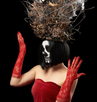 Femme d'apparence caucasienne avec maquillage squelette se dresse dans une robe en velours rouge