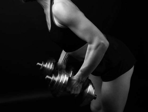 Une femme d'apparence caucasienne tient des haltères en acier dans ses mains