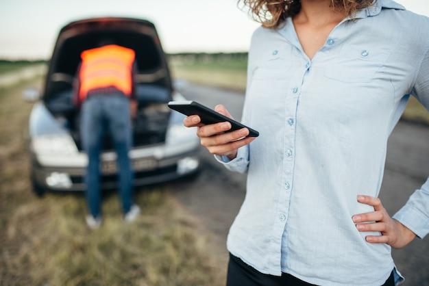 Femme appelle au service, l'homme répare une voiture cassée