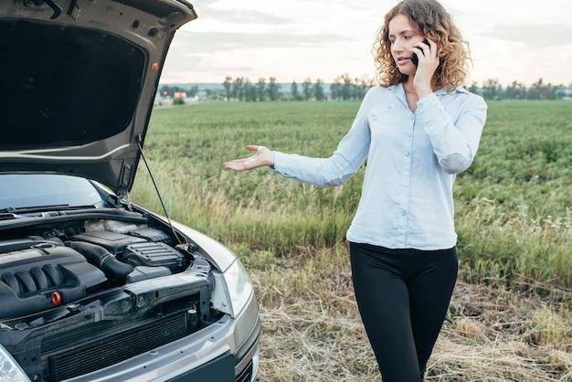 Femme appelle au service d'urgence, voiture cassée