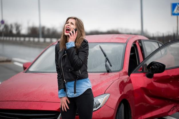 Une femme appelle un service debout près d'une voiture rouge