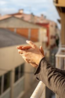 Femme applaudissant dans un balcon d'espagne saluant les travaux des médecins, des infirmières, des politiques