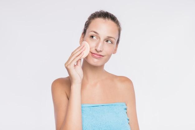 Femme, application, éponge faciale