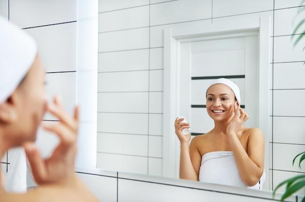 La femme appliquant la crème au visage avec le doigt tout en regardant son reflet dans le miroir de la salle de bain