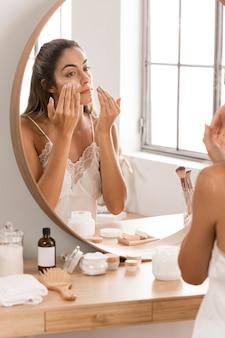 Femme appliquant la crème dans le miroir
