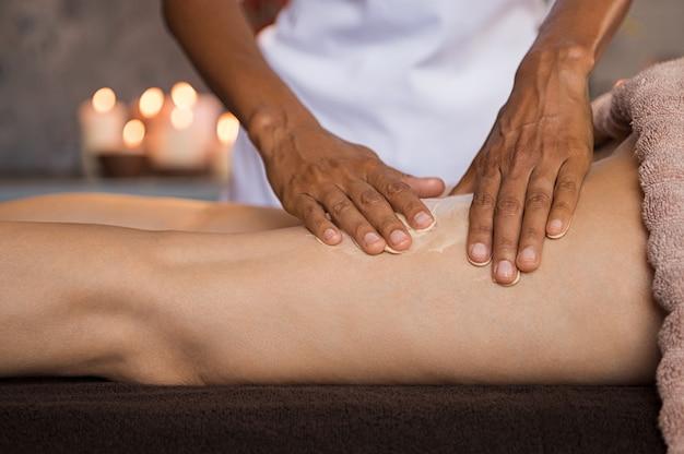 Femme appliquant une crème hydratante pour le massage des jambes