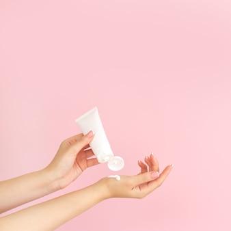 Femme appliquant la crème hydratante de soins de la peau cosmétique sur fond rose