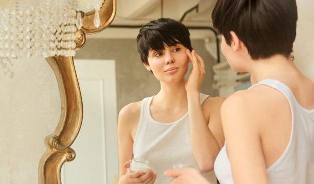 Femme appliquant une crème hydratante sur son visage routine cosmétique quotidienne de soins de la peau de beauté