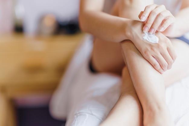 Femme appliquant la crème pour les mains après s'être baignée sur ses jambes concept de soins de santé de la main