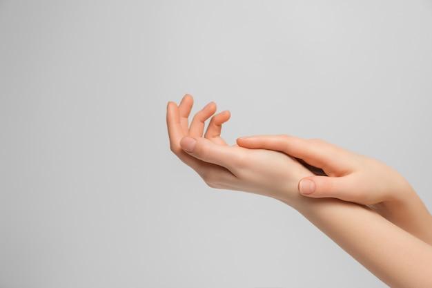 Femme appliquant la crème pour les mains.