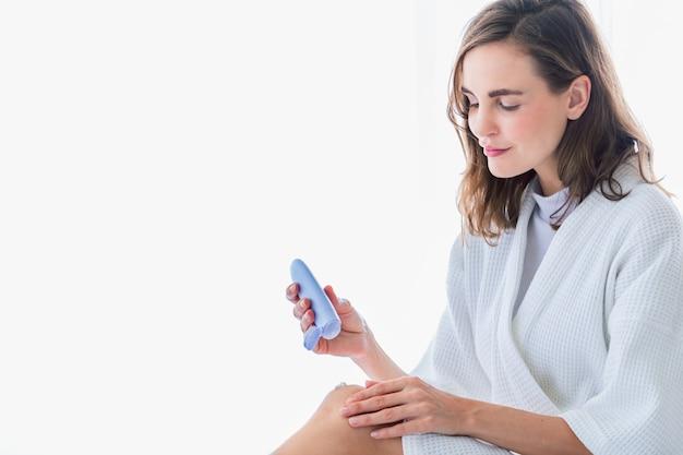 Femme appliquant une crème rafraîchissante ou une lotion pour le corps sur ses jambes et ses mains