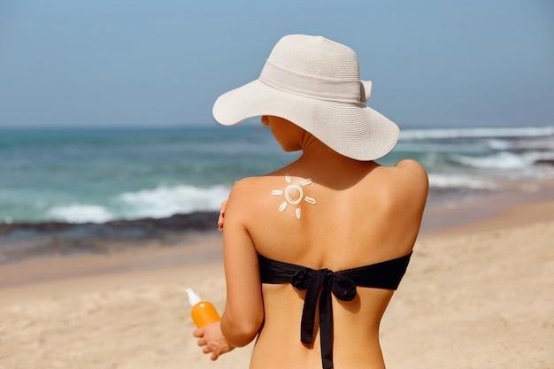 Femme appliquant la crème solaire sur l'épaule bronzée sous la forme du soleil.