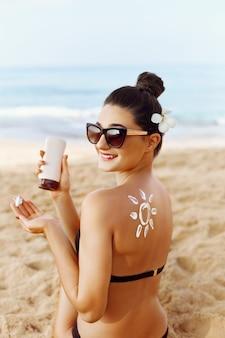Femme appliquant la crème solaire sur l'épaule bronzée sous la forme du soleil