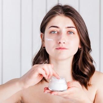 Femme appliquant la crème sur le visage