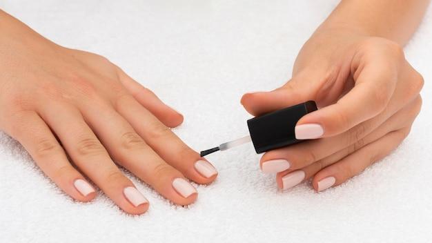 Femme appliquant du vernis à ongles