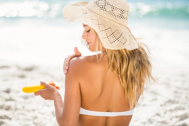 Femme appliquant un écran solaire