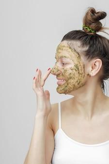 Femme appliquant exfoliant sur son visage
