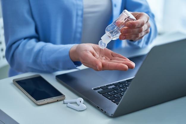 Femme appliquant un gel antiseptique antibactérien pour la désinfection et le nettoyage des mains tout en travaillant sur un ordinateur pour se protéger contre une épidémie de coronavirus