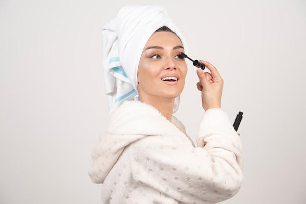 Femme appliquant le mascara en serviette et peignoir.