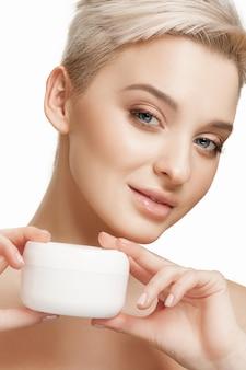 La femme applique la crème hydratante sur le visage au studio