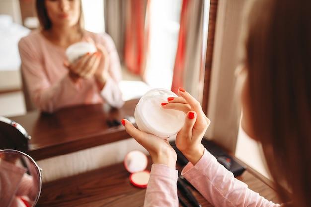Femme applique de la crème pour les mains sur la peau au miroir