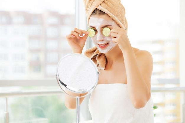 Femme applique un masque d'argile blanche pour les soins du visage dans la salle de bains de luxe de l'hôtel