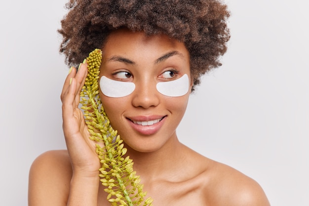 La femme applique des patchs de beauté sous les yeux tient une plante sauvage près du visage sourit doucement regarde au loin se tient les épaules nues sur blanc