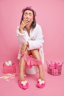 Une femme applique des rouleaux de cheveux des patchs de beauté porte un peignoir blanc une culotte en dentelle rose est assise sur la cuvette des toilettes les procédures de soins de la peau se prépare pour les poses de fête dans les toilettes seules