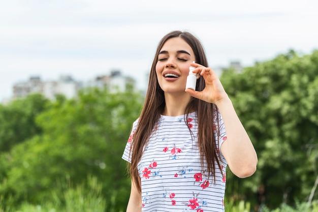 Femme applique un spray nasal