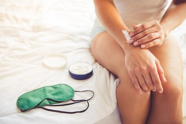 Femme, appliquer la crème pour les mains en position assise sur le lit à la maison.