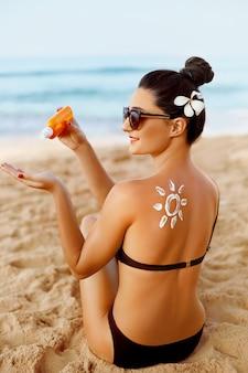 Femme appliquer une crème de protection solaire sur son épaule bronzée
