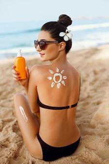 Femme appliquer la crème solaire sur le dos bronzé