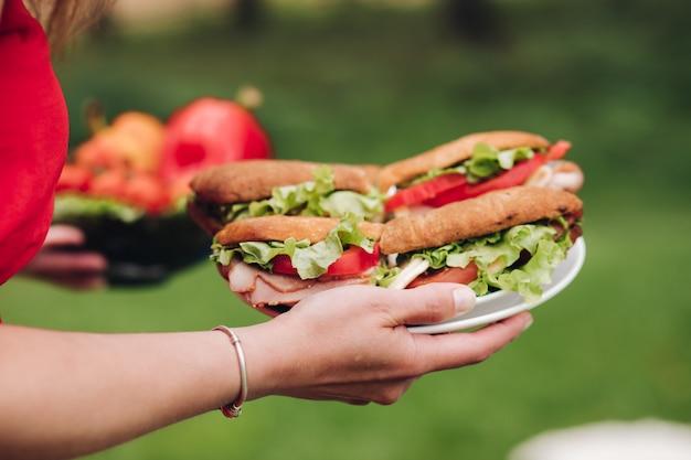 Femme apportant des sandwichs frais.
