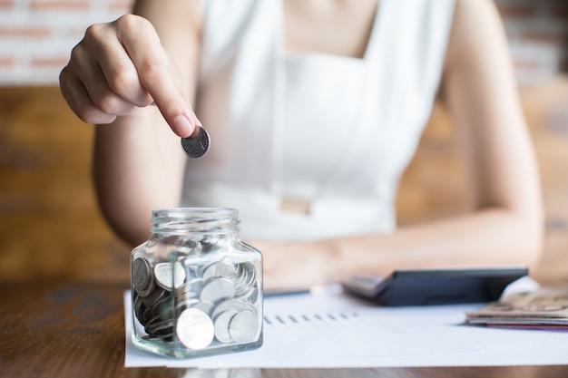 La femme apporte une pièce de monnaie dans une bouteille de verre sur le bureau.
