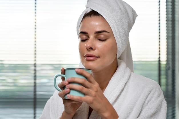 Femme appréciant du café après son bain
