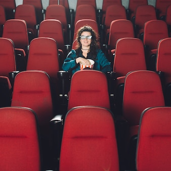 Femme appréciant le film dans l'auditorium vide