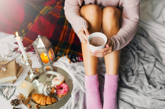 Femme appréciant l'heure du matin dans son lit, portant un pull en laine confortable et des chaussettes roses, tenant une grande tasse de café.