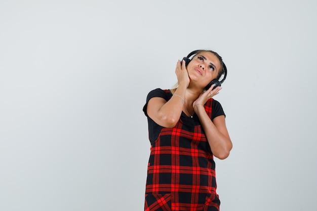 Femme appréciant la musique avec des écouteurs en robe chasuble et à la rêveuse, vue de face.