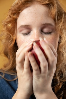 Femme appréciant l'odeur d'une pomme