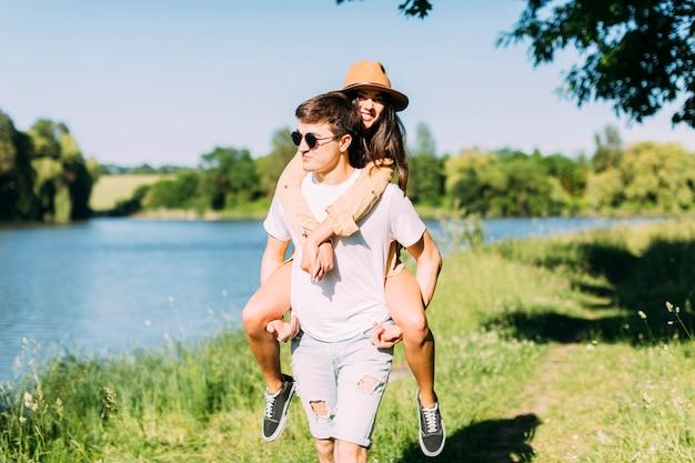 Femme appréciant piggyback ride sur les copains de retour à l'extérieur